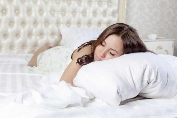 Woman sleeping holding pillow